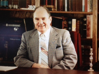 George W. Southwick, sitting behind the desk in his library