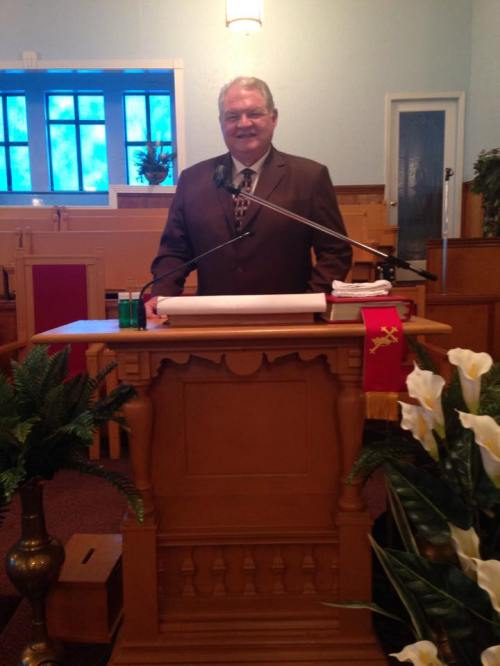 Dr. Byron Klaus, standing in the original pulpit in St. Paul Church of God in Christ, Lexington, MS. Bishop Mason preached from this pulpit.